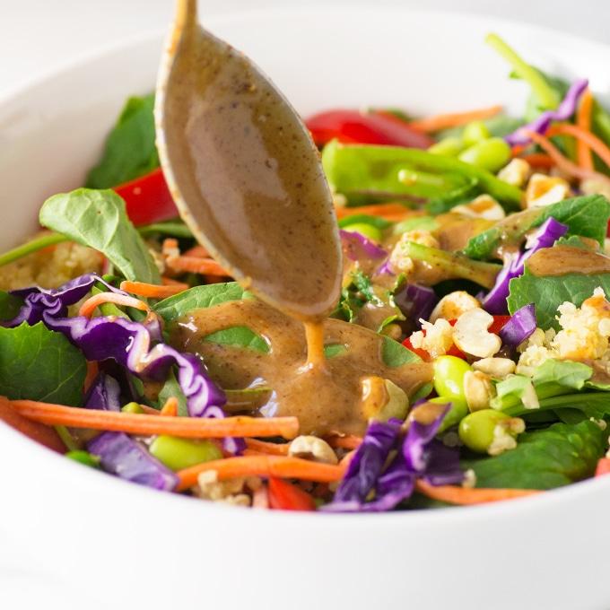 spoon pouring peanut sauce on salad
