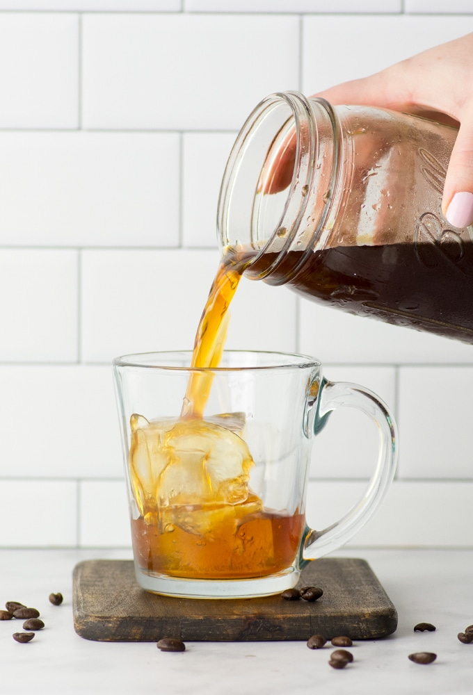 pouring coffee into mug from mason jar