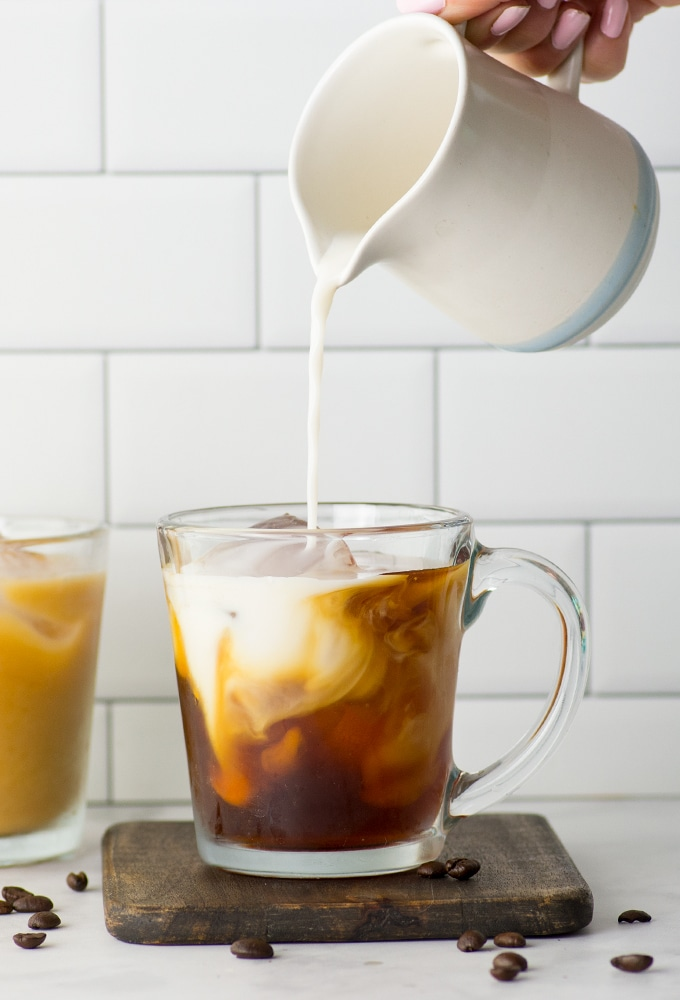pouring almond milk into mug of cold brew coffee