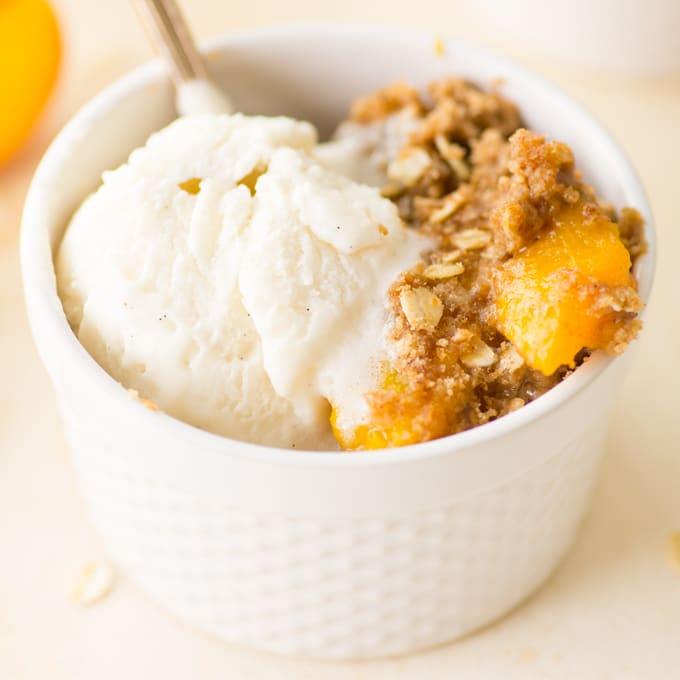 vegan peach crisp with vanilla ice cream in ramekin