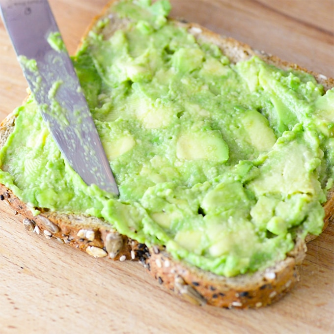 knife spreading avocado onto toast