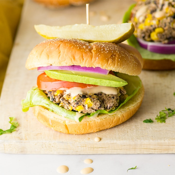 black bean and corn burger with lettuce, tomato, avocado, red onion, and pickle