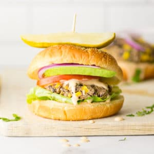 black bean and corn veggie burger on bun with lettuce, tomato, red onion, and avocado.