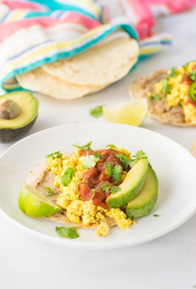 vegan huevos rancheros on a plate with salsa and avocado
