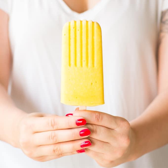 hand holding mango popsicle