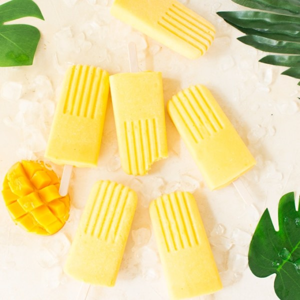 mango popsicles on pink background