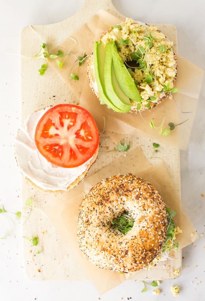 everything bagel, cream cheese, tomato and avocado on wood board