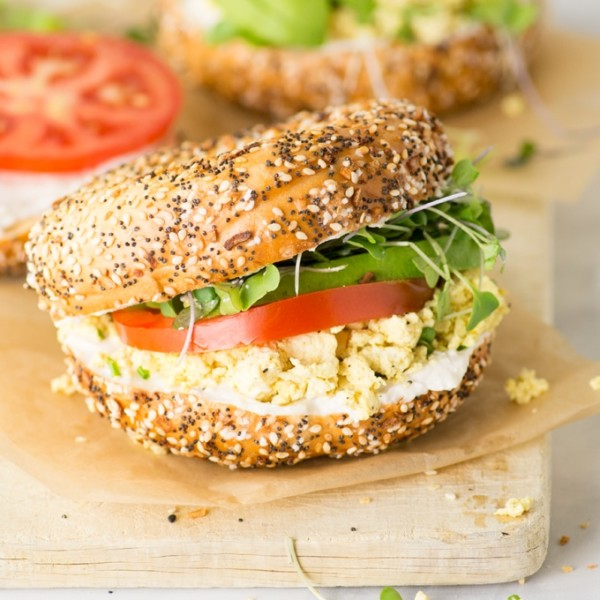 vegan breakfast sandwich on everything bagel with avocado, tomato, tofu scramble, sprouts