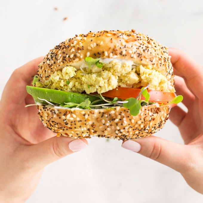 hands holding breakfast sandwich on everything bagel