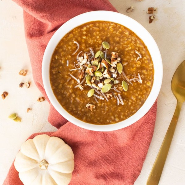 bowl of pumpkin oatmeal with orange napkin and white pumpkin