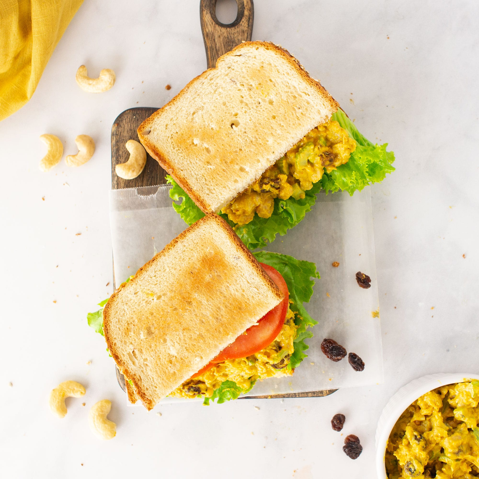 overhead view of vegan curried chickpea salad sandwich with raisins and cashews on marble background