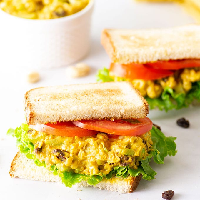 vegan chickpea salad sandwich on marble background with lettuce and tomato