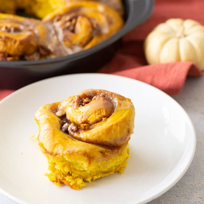 vegan pumpkin cinnamon roll on white plate with baking pan in background
