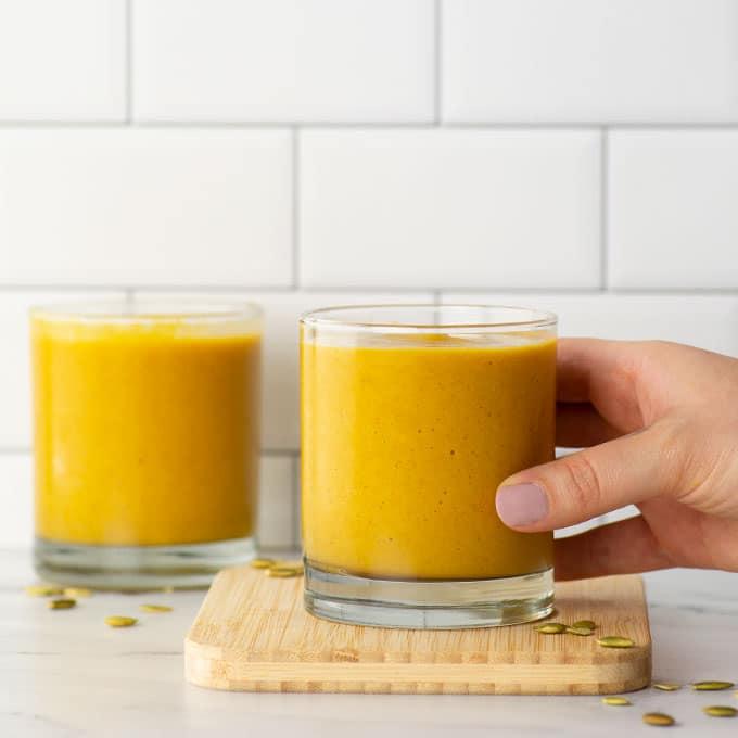 hand holding glass of pumpkin pie smoothie