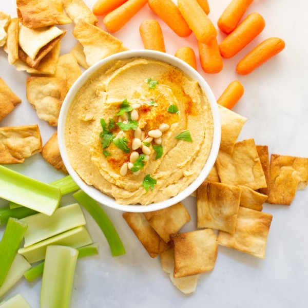 overhead view of hummus with pitta chips, carrots, and celery