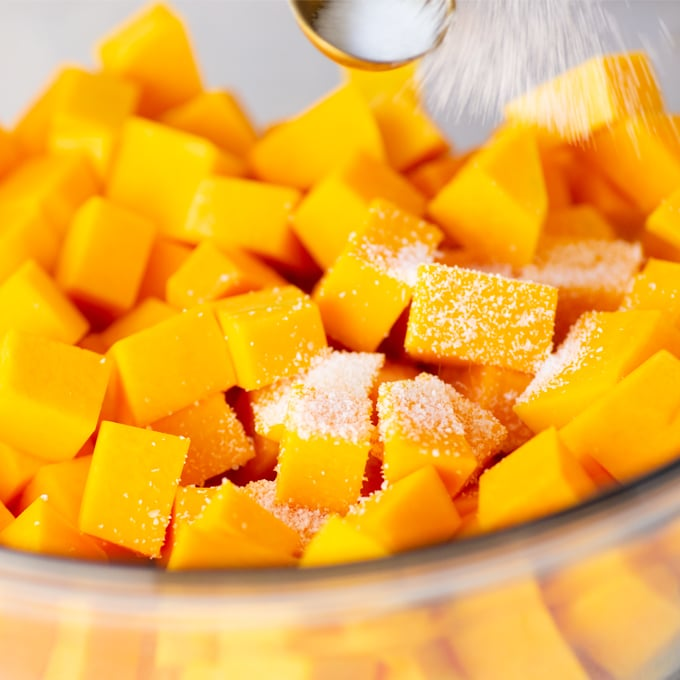 pouring salt over butternut squash cubes