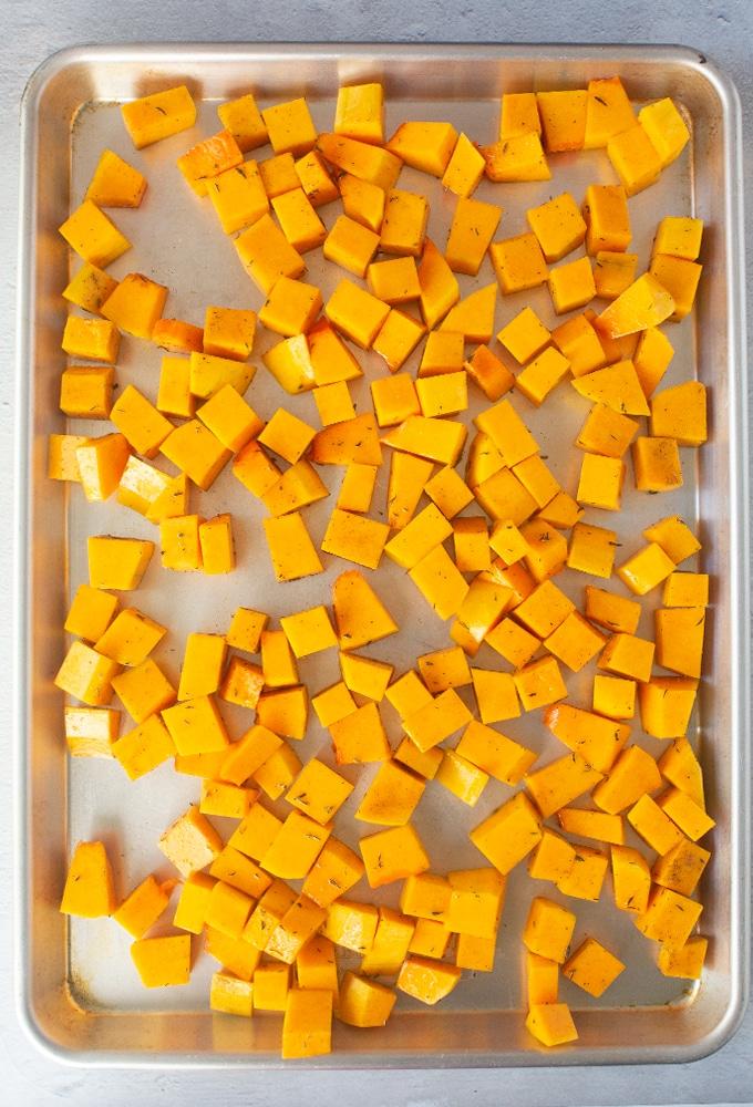 butternut squash cut into cubes on baking sheet