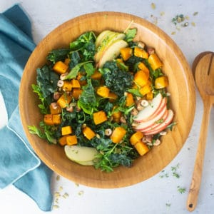 salad with kale, apples, squash, and hazelnuts in wood salad bowl
