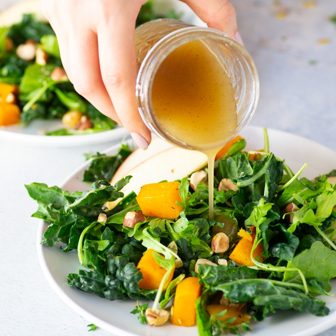 hand pouring homemade dressing over kale and apple salad