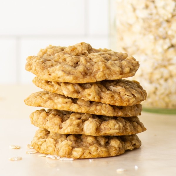 stack of vegan oatmeal cookies with oats in the background
