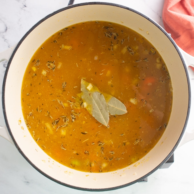 vegan soup in pot with bay leaf on top