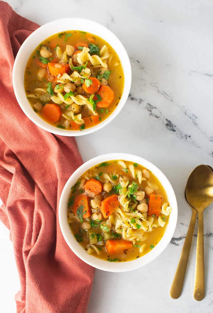 two bowls of chickpea noodle soup on marble background with gold spoons