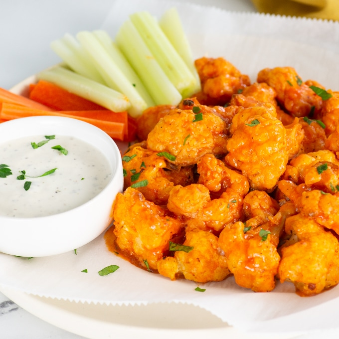 vegan buffalo cauliflower bites on a plate with dip, celery, and carrots