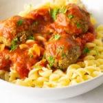 close up of vegan tofu meatballs on pasta with marinara sauce