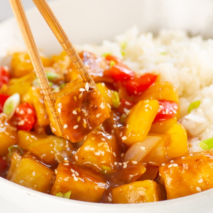 chopsticks holding sweet and sour tofu over bowl