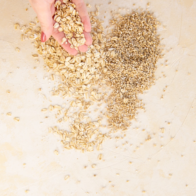steel-cut oats and rolled oats on cream background