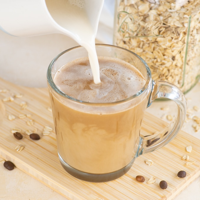 pouring homemade oat creamer into mug of coffee