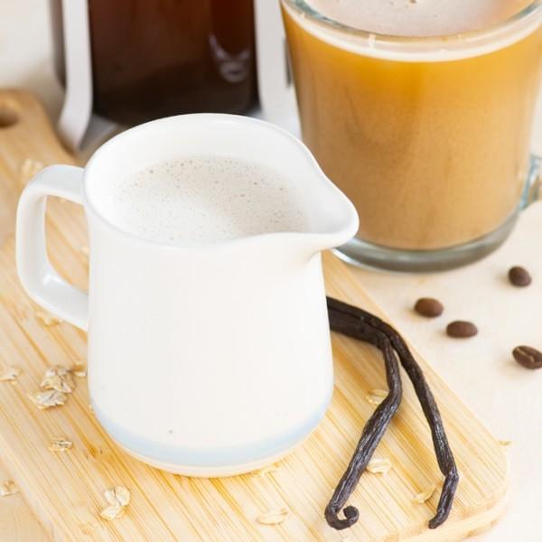 homemade oat milk creamer on wood board with vanilla beans