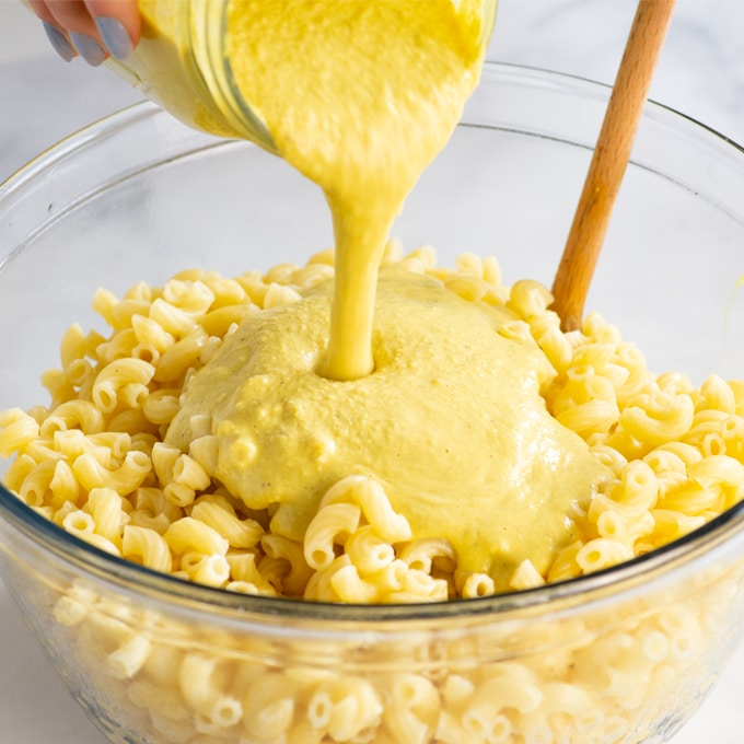 hand pouring vegan cheese sauce over bowl of macaroni