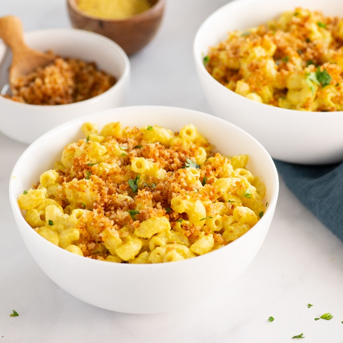 vegan mac and cheese topped with breadcrumbs in a white bowl.