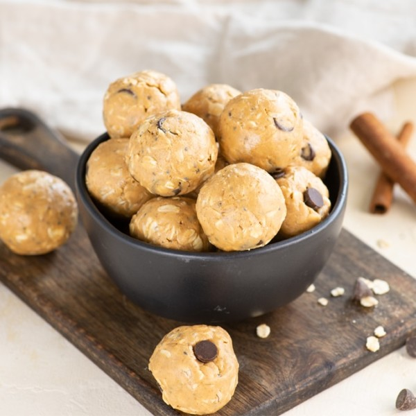 chai vegan energy bites in black bowl on wood cutting board with chocolate chips