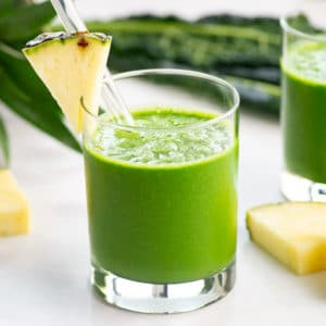 vegan pineapple kale smoothie garnished with fresh pineapple