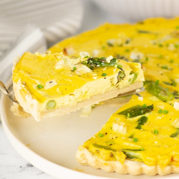 slice of vegan quiche topped with leeks and asparagus