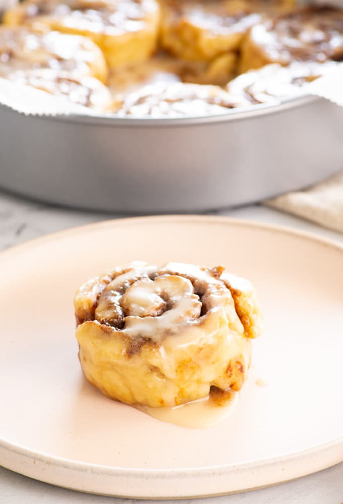 cinnamon roll on plate with pan of cinnamon rolls in background
