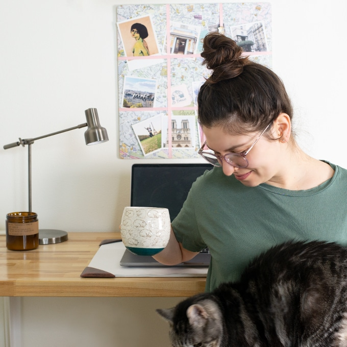 girl with hair in bun holding coffee and petting cat