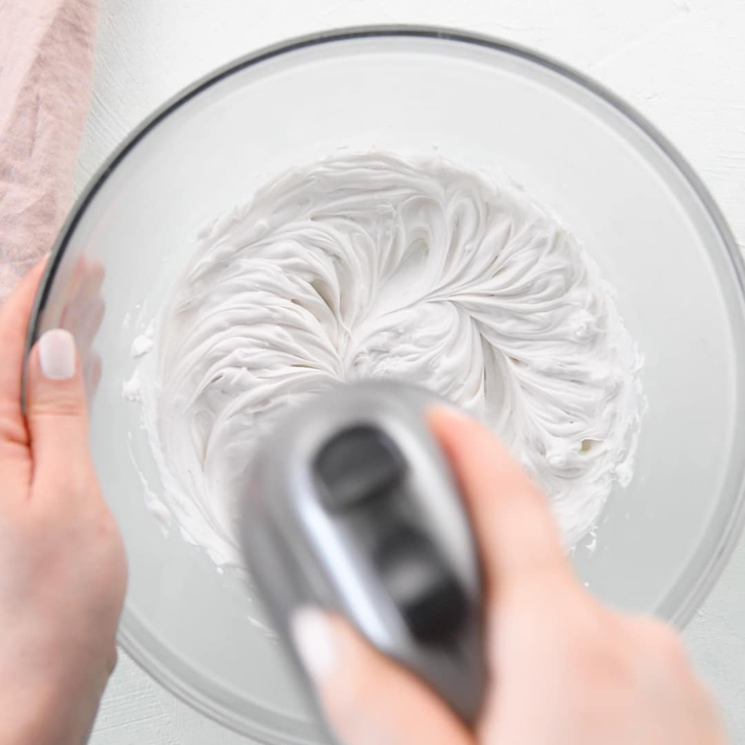 hands mixing coconut whipped cream in mixing bowl