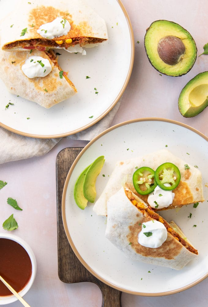 two vegan crunchwrap supremes on plates with avocado