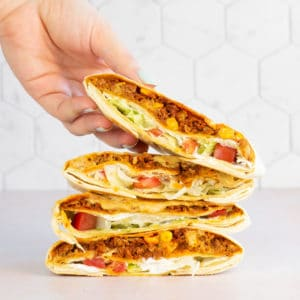 stack of crunchwrap supremes and hand grabbing top one