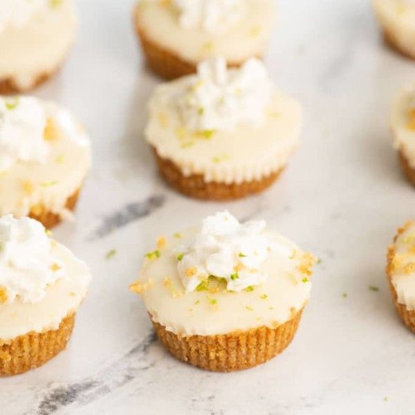 vegan key lime pie bites on marble background. bites are topped with graham cracker crumbs, lime zest, and vegan whipped cream