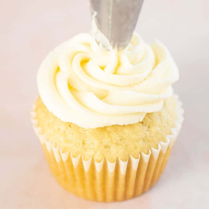 frosting vanilla cupcake with piping bag