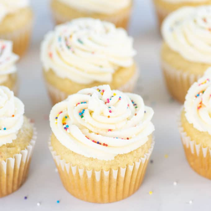 closeup of vegan vanilla cupcake with rainbow sprinkles