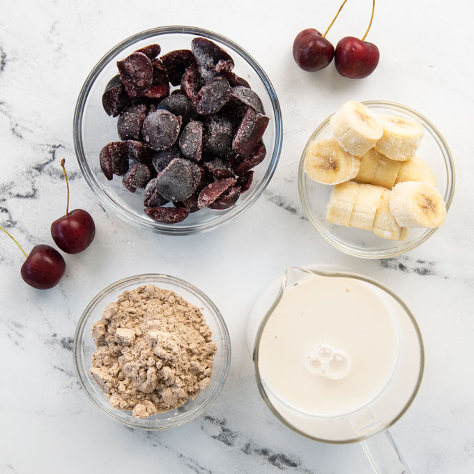 almond milk, cherries, bananas, and protein powder on a marble background
