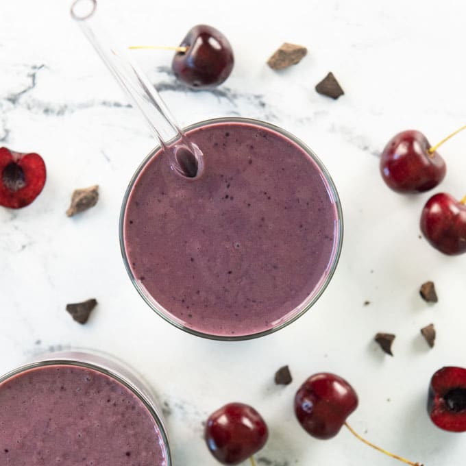 overhead shot of a cherry smoothie with fresh cherries and chocolate pieces