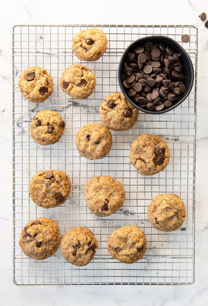 chocolate chip cookies on a cooling rack with a bowl of chocolate chips