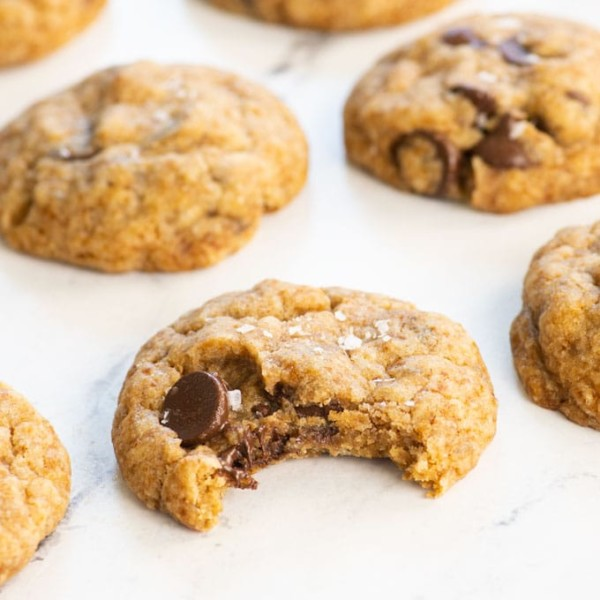 chocolate chip cookies on white background with a bite taken out of one
