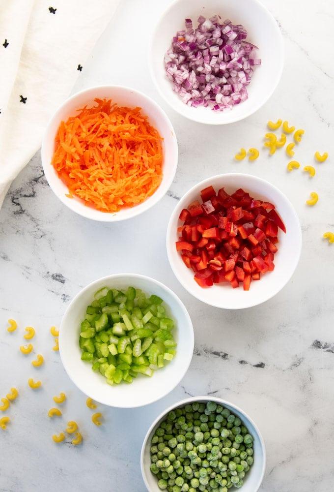chopped veggies in white bowls